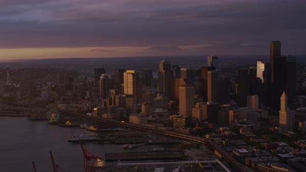 Aerial shot of Seattle Great Wheel near Elliott Bay at dusk, modern Seattle cityscape in background, Washington, United States of America Rights-managed stock video