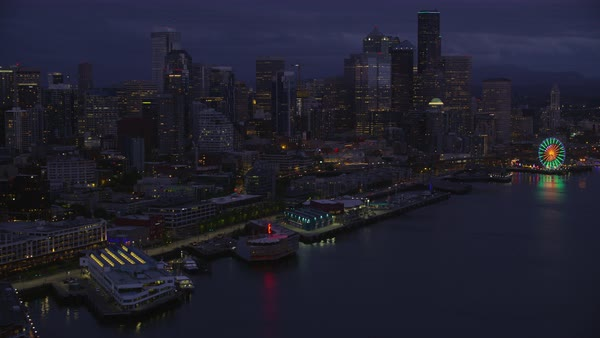 Aerial shot of Seattle Great Wheel near Elliott Bay at night, modern Seattle cityscape in background, Washington, United States of America Rights-managed stock video
