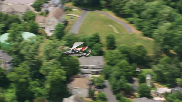 Aerial shot of a helicopter flying above a suburban area with sports fields Rights-managed stock video