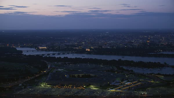 Aerial shot of the illuminated Pentagon with Washington DC cityscape at dusk Rights-managed stock video