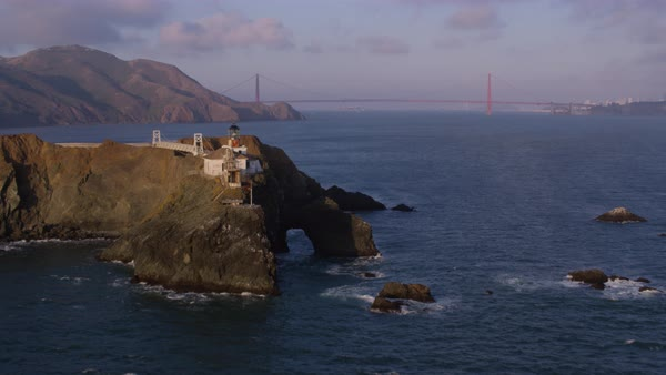 Aerial shot of flying past Point Bonita Lighthouse toward Golden Gate Bridge Rights-managed stock video