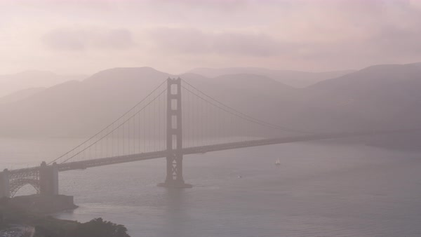 Aerial shot of Golden Gate Bridge at dusk seen through haze Rights-managed stock video