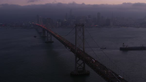 Aerial shot of San Francisco-Oakland Bay Bridge with skyline of San Francisco Rights-managed stock video