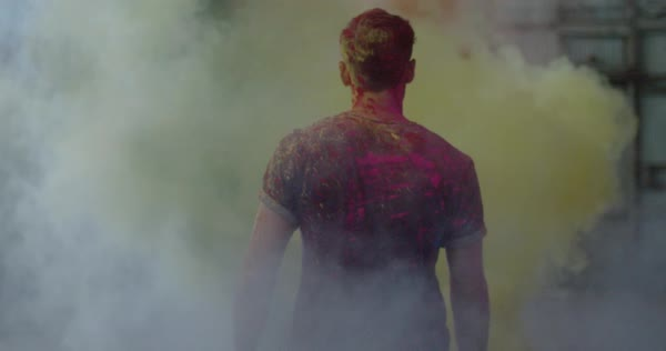 Tracking shot of man walking into a cloud of powder paint Royalty-free stock video