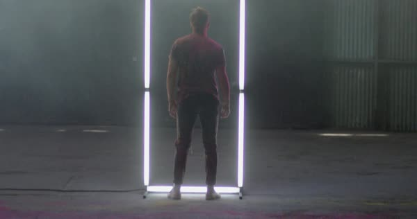 Hand-held shot of a man standing in front of a frame made of tube lights Royalty-free stock video