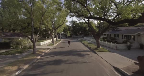 Drone shot of a young man skateboarding on a suburban street Royalty-free stock video