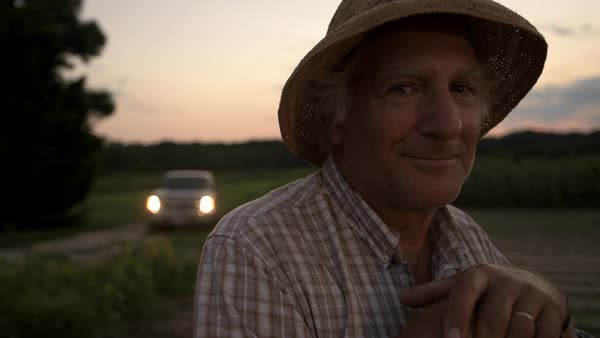 Hand-held shot of an elderly farmer smiling at camera Royalty-free stock video