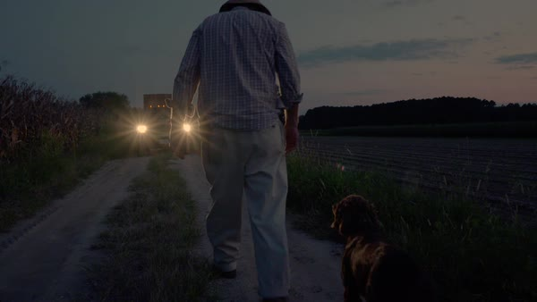 Slow motion shot of a farmer walking to a pickup truck with his dog Royalty-free stock video