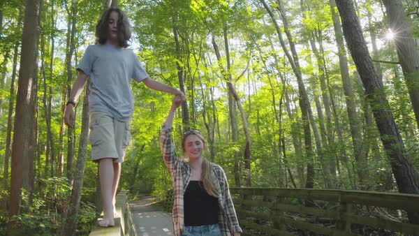 Hand-held shot of a boy walking on bridge railing while holding hand of a woman Royalty-free stock video