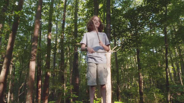 Hand-held shot of a boy imitating drumming with two sticks in a forest Royalty-free stock video