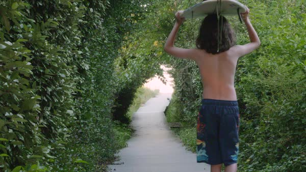 Slow motion shot of a boy carrying a surfboard on his head Royalty-free stock video