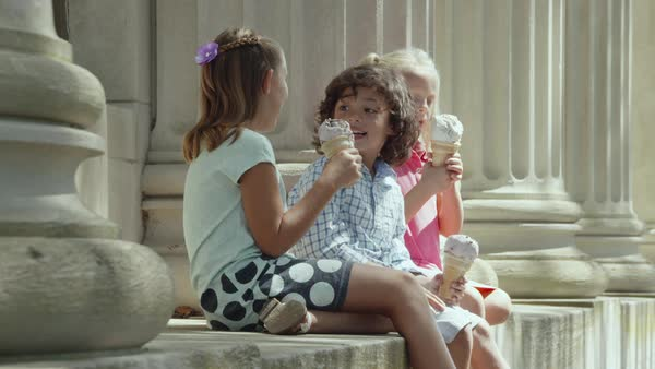 Static shot of three children talking and eating ice cream Royalty-free stock video