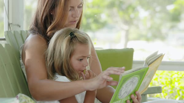 Zooming out shot of a mother and her daughter reading a book Royalty-free stock video