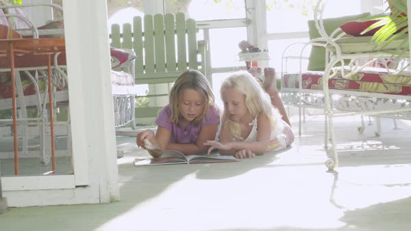 Slow motion shot of two girls reading a book while lying on floor Royalty-free stock video