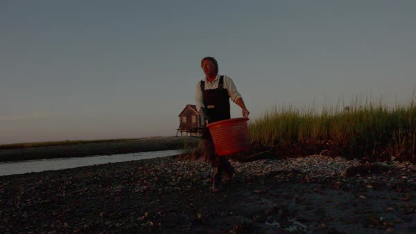 Hand-held shot of a fisherman walking on a shore with a basket of oysters Royalty-free stock video