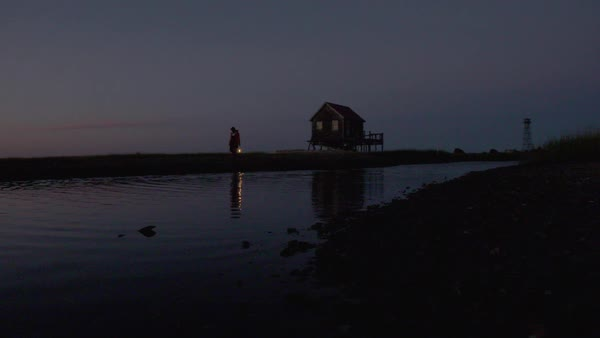 Slow motion shot of a fisherman walking away from a stilt house with a lantern Royalty-free stock video
