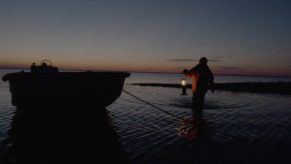 Slow motion shot of fisherman putting a lantern on a boat Royalty-free stock video