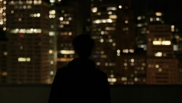 Hand-held shot of a man viewing illuminated skyscrapers from a rooftop Royalty-free stock video