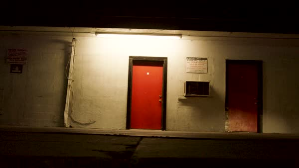 Exterior of a run-down building with two doors at night Royalty-free stock video