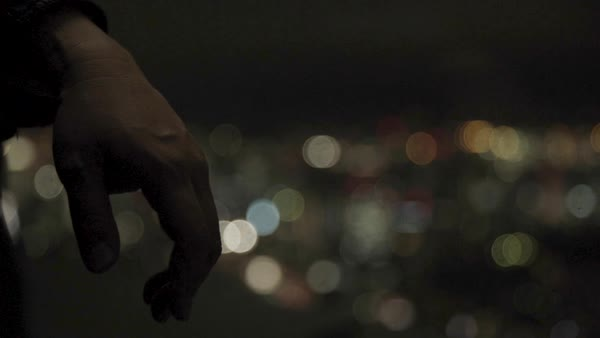Hand-held shot of hand of a man with lights of Tokyo in background at night Royalty-free stock video