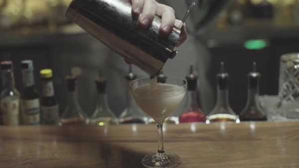 Hand-held shot of a bartender pouring a cocktail into a glass Royalty-free stock video