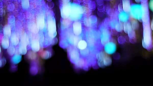 Silhouettes pass under a dazzling array of colorful flashing lights. Royalty-free stock video