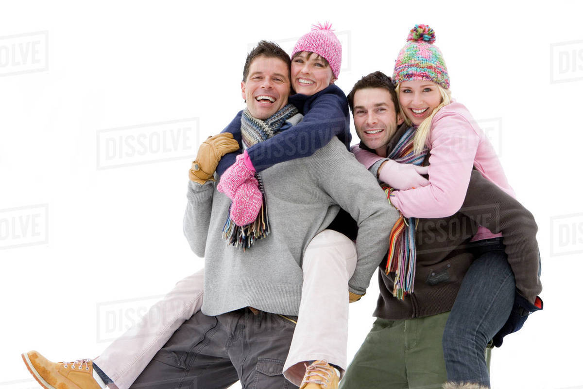 Two young couples in winter clothing, portrait, men carrying women on  backs, cut out stock photo