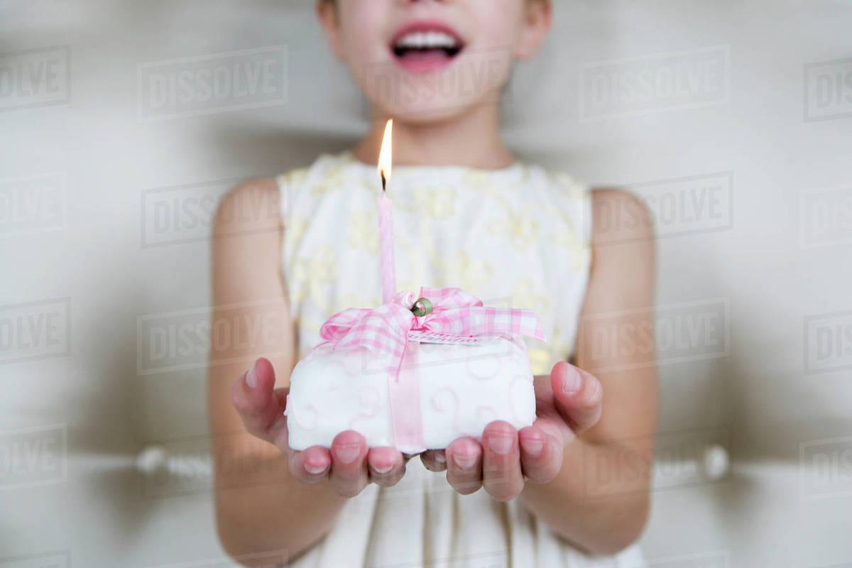 Little Girl Holding A Birthday Cake With Lit Candles Stock Photo