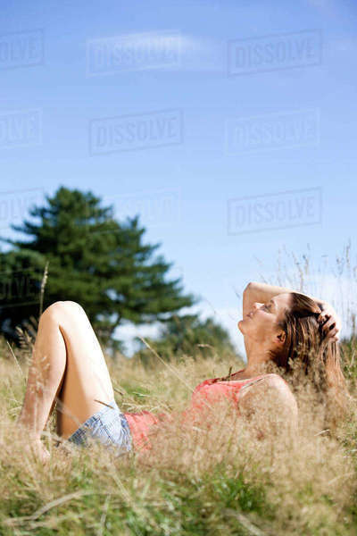 A young woman lying on the grass, enjoying the sunshine Royalty-free stock photo