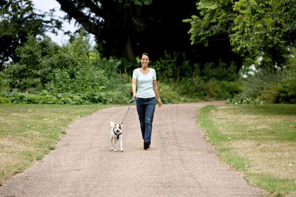 A young woman walking her dog in the park Royalty-free stock photo
