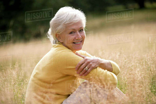 A senior woman sitting on the grass, smiling Royalty-free stock photo