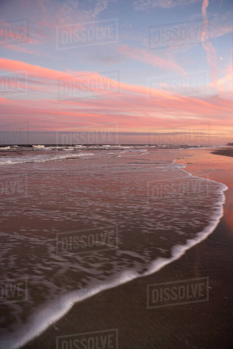 View from sandy beach of picturesque red sunset, horizon over sea, surf  lapping on shore stock photo