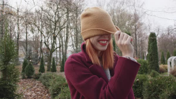 A young woman laughing and covering her face with a cap while standing in a park Royalty-free stock video
