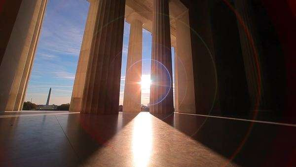 A tracking shot with a lens flare of the bottom of the pillars of the Lincoln Memorial in Washington DC at sunset Royalty-free stock video