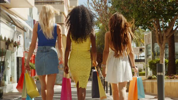 Three women walking away from camera with shopping bags in town Royalty-free stock video