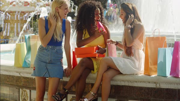 Three women sitting by fountain looking at new shoes Royalty-free stock video