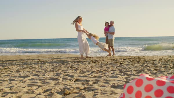 Young family on beach playing and twirling Royalty-free stock video