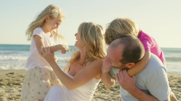 Young family sitting on beach with children and parents hugging Royalty-free stock video