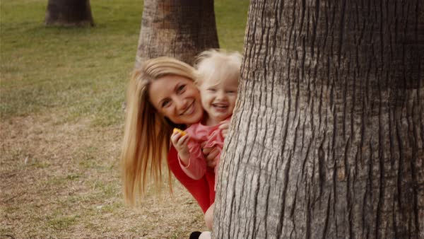 Mother and daughter hiding behind tree trunk in park Royalty-free stock video