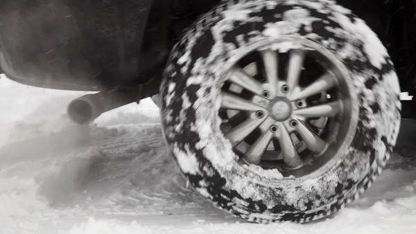 Close up of black SUV rear wheels spinning in the snow. Royalty-free stock video