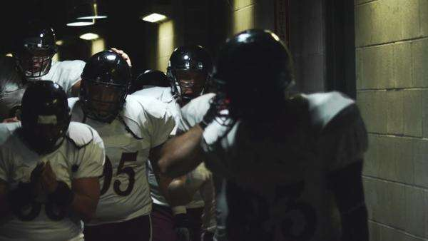 An excited football team walks down a dark tunnel towards the field before a game Royalty-free stock video