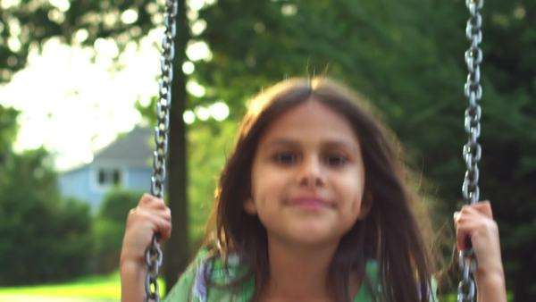 Cute little girl on a swing smiles for the camera. Medium shot. Royalty-free stock video