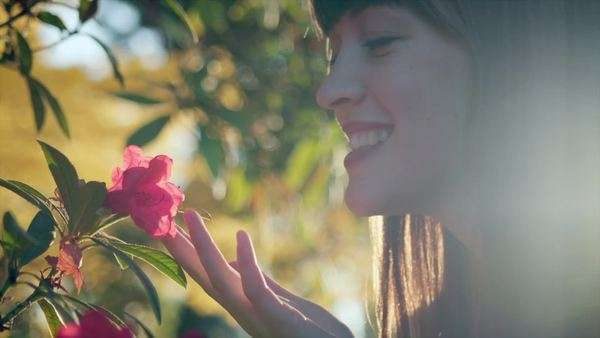 Close up of a woman smelling and flower and then smiling, in slow motion Royalty-free stock video