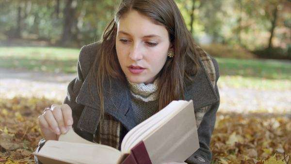 Close up of a young woman laying in a pile of leaves and reading a book in the park Royalty-free stock video