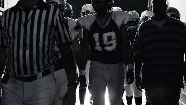 A football team walks down a dark hallway before a game Royalty-free stock video