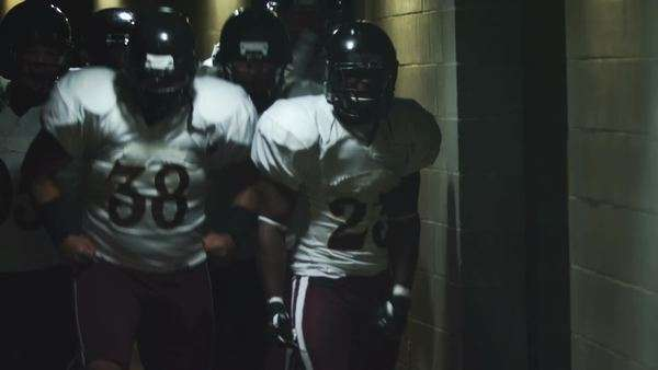 Excited football players jump and run down a tunnel before a game Royalty-free stock video