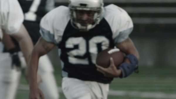 Close up of a running back sprinting down the field with the ball Royalty-free stock video
