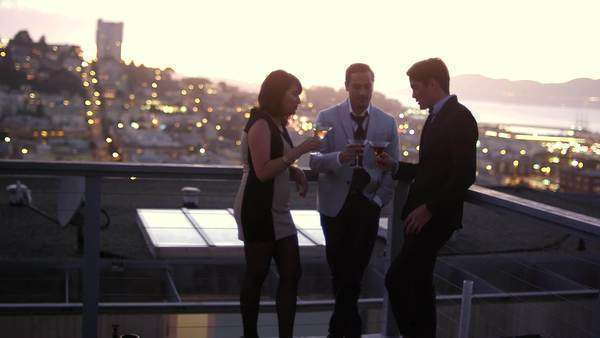 Friends hang out and have cocktails on a roof at sunset, with San Francisco in the background Royalty-free stock video
