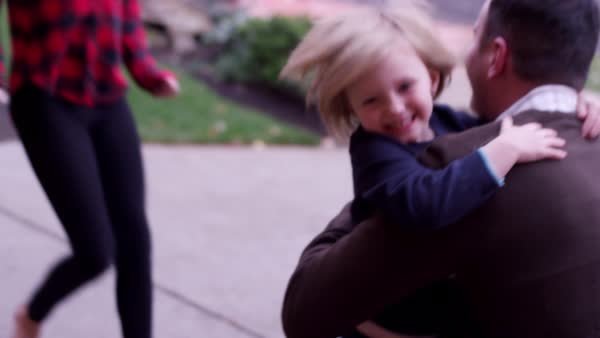 A father getting home from work gives his three kids a big group hug Royalty-free stock video