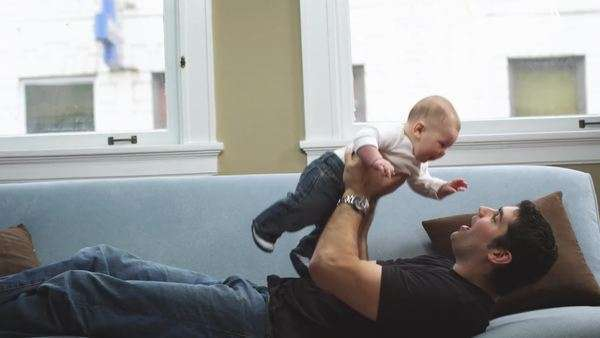 A man lays on the couch and lifts a baby above his head into the air Royalty-free stock video